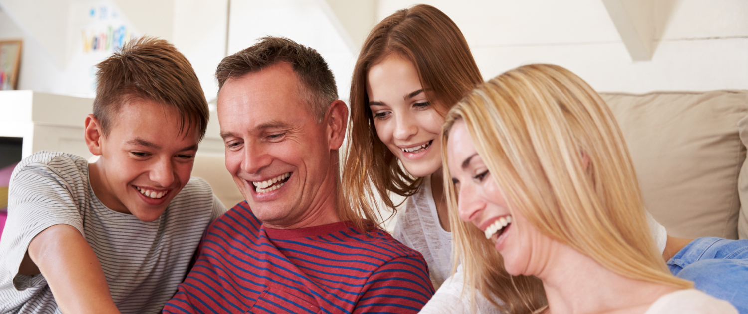 Image of a family (son, father, daughter and mother) all smiling